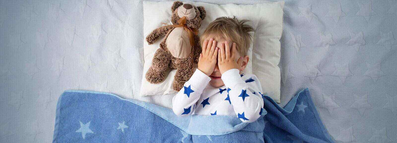little boy in bed with a teddy bear