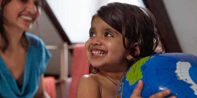 fille qui tient un globe terrestre et sourit à son professeur