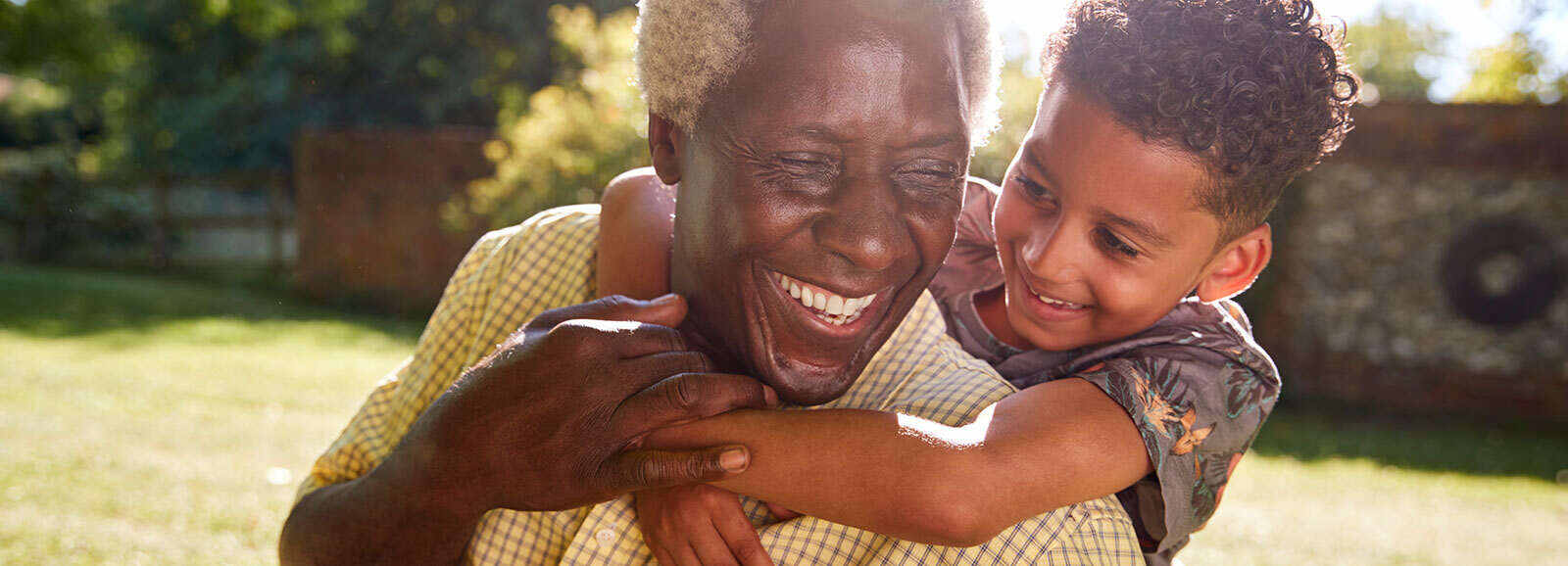 père souriant, qui porte son fils sur ses épaules