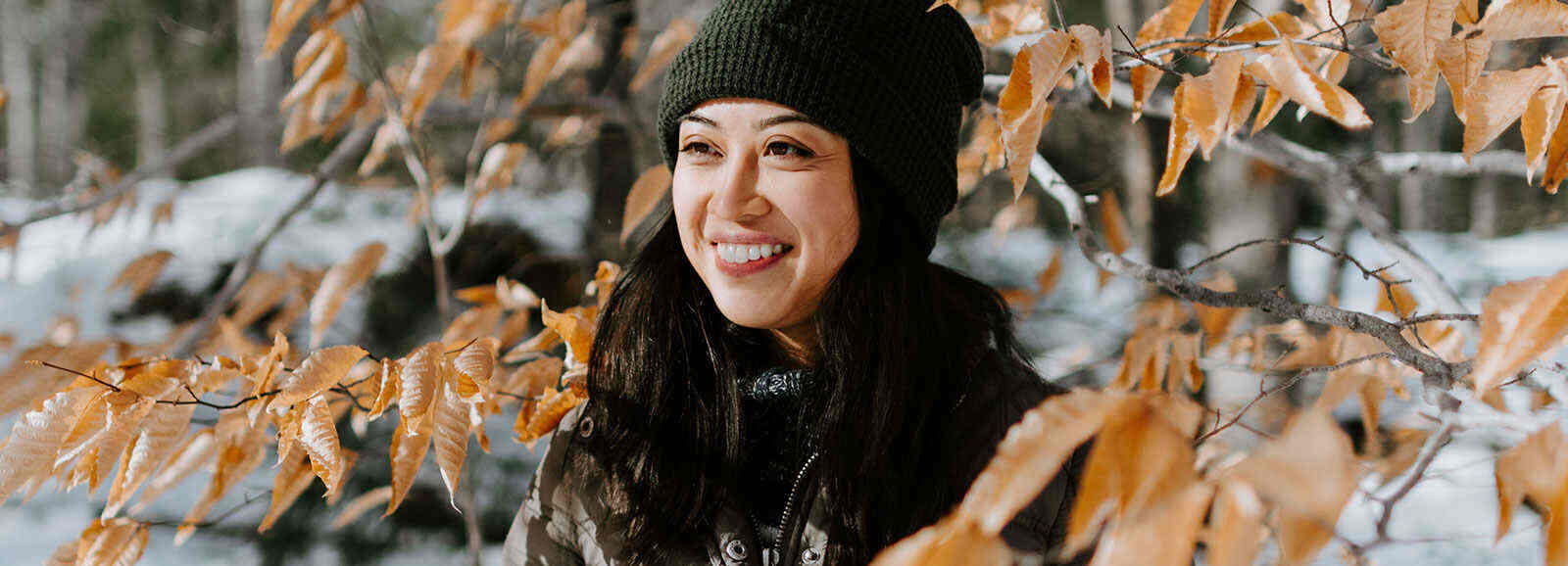 femme souriante, qui porte un manteau et un chapeau