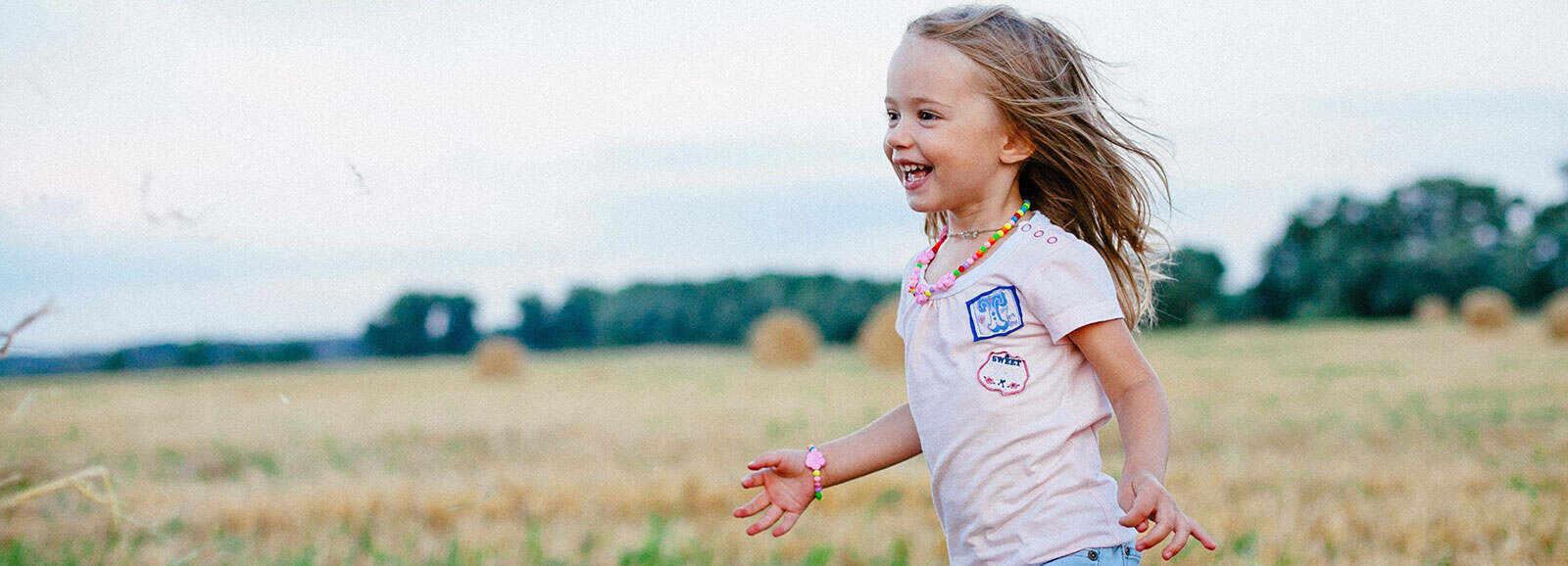petite fille qui court dans un champ