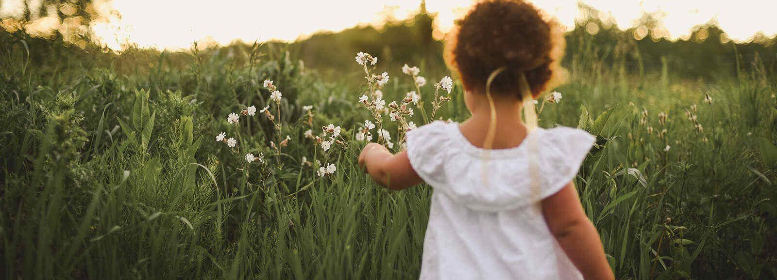 petite fille en robe blanche, qui regarde des fleurs des champs